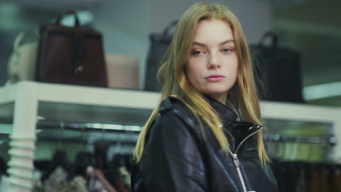 Young beautiful girl trying on a leather jacket in the store Live Action