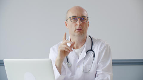 Professional doctor talking with patient and looking at camera GIF