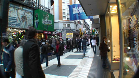 People walk shop and window shop on a busy street Stock Video Footage