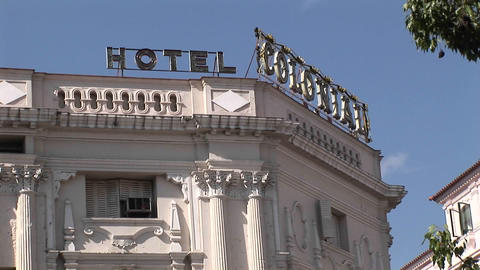 A sign at the top of a building with a terra cotta facade reads Hotel Colonial Footage