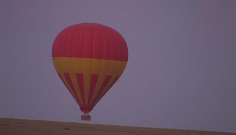 A hot air balloon rises from off the ground Footage