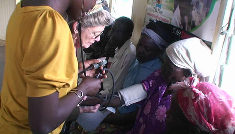 An older African woman gets her blood-pressure read Stock Video Footage