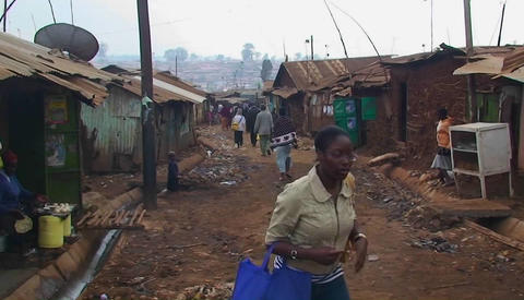 People walk down a dirty street in a shanty town Stock Video Footage