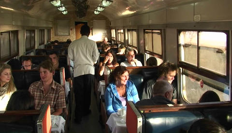An attendant passes through a train car carrying a plate, as passengers talk and look out the window Footage