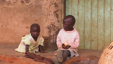Two children eat on the steps of a very modest dwelling Stock Video Footage