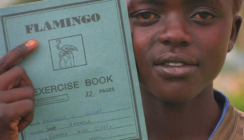 A young boy holds up his notebook, pointing to the wording and picture Footage