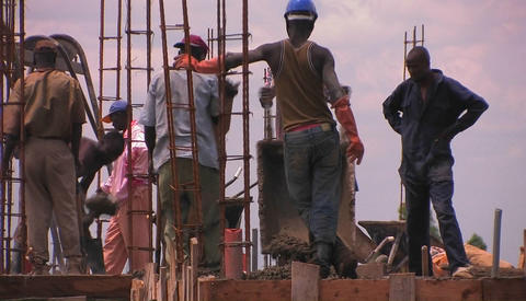 A crew of men work on constructing a building Footage