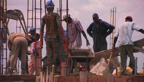 A crew of men work on constructing a building Stock Video Footage