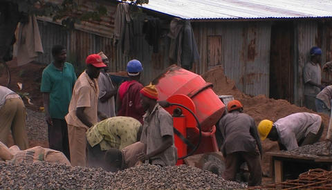 Men on a work site shovel and mix cement Stock Video Footage