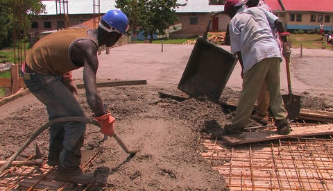 Men dump and spread concrete for the floor of a building Stock Video Footage