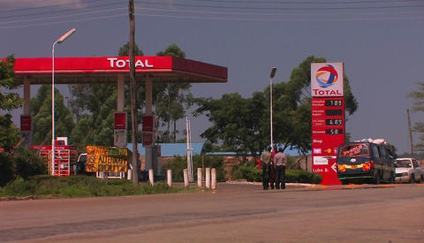 Three men talk in front of a gas station Stock Video Footage