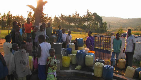 People filling up canisters with water from a water pump Footage