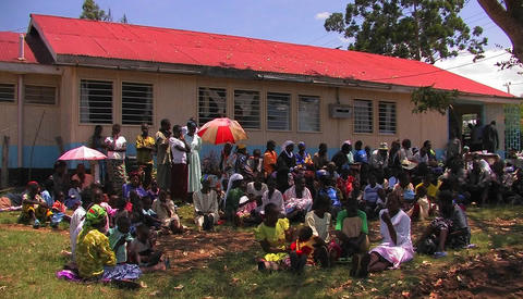 A group of Africans sit in the shade in front of a building Stock Video Footage
