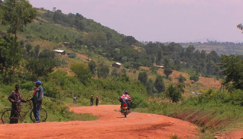 A person on a motorbike pulls to the side of a rural road Stock Video Footage