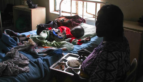 A woman sits next to the bed of a child in a hospital and... Stock Video Footage