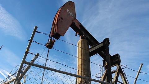 An oil derrick pumps oil Stock Video Footage