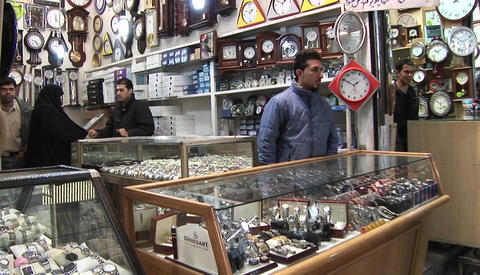 A vendor sells clocks in a bazaar in Iran Stock Video Footage