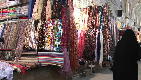 Women in chadors pass carpets in a bazaar in Iran Stock Video Footage