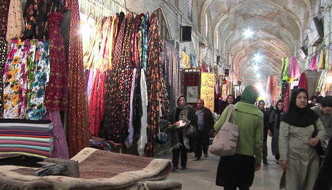 Women in chadors pass carpets in a bazaar in Iran Footage