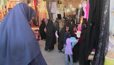 Women wearing headscarfs and chadors pass through a... Stock Video Footage