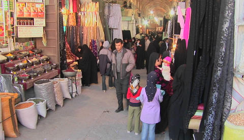 Women wearing headscarfs and chadors pass through a bazaar in Iran Footage