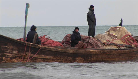 Fishermen pass on a traditional style boat in Iran Stock Video Footage
