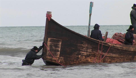 Fishermen pass on a traditional style boat in Iran Footage