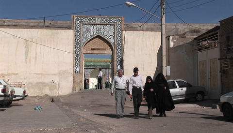 Two women wearing chadors and two men pass on a street in Iran Live Action
