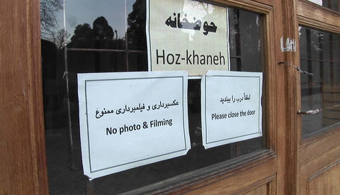 "Signs on a window in Iran. One reads ""Hoz-khaneh."" The others prohibit photography and ask visitor Footage"