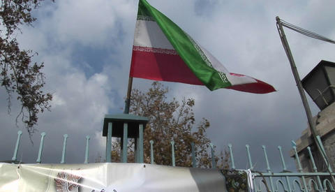 The Iranian flag flies atop a gate Stock Video Footage
