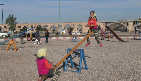 Children play on a see-saw in Iran Stock Video Footage