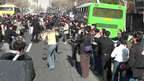Protesters march down a busy street in Iran Stock Video Footage
