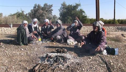 Men wearing the traditional muslim headdress, or keffiyeh, sit by a fire outside in Iran Footage