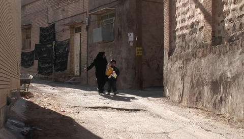 A woman wearing a chador walks with two children down an... Stock Video Footage
