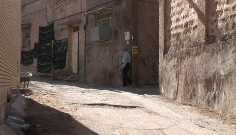 A woman wearing a chador walks with two children down an ancient alley in Iran Footage
