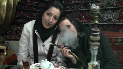Women in headscarfs smoke a hookah pipe in a cafe in Iran Stock Video Footage