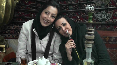 Women in headscarfs smoke a hookah pipe in a cafe in Iran Stock Video Footage