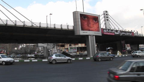 A busy thoroughfare in a city in Iran with a modern, digital billboard Footage