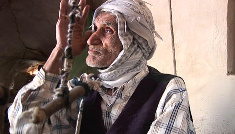 An elderly man wearing a keffiyah speaks in Iran Footage