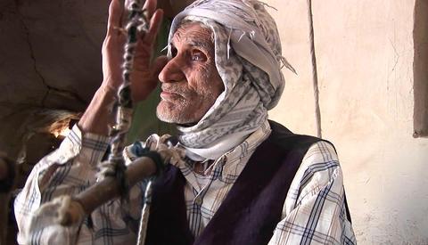 An elderly man wearing a keffiyah speaks in Iran Footage