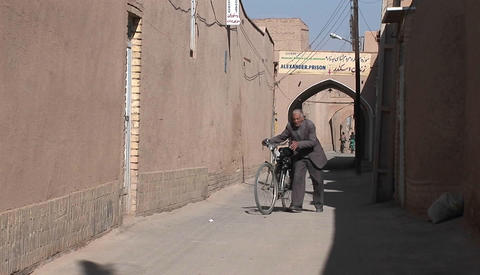 Two children ride bicycles down an ancient alley way in Iran Stock Video Footage