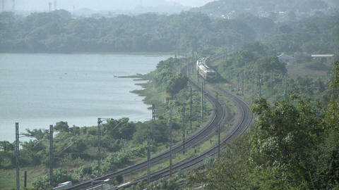 An approaching train travels a rural route near a lake Stock Video Footage