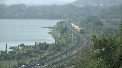 An approaching train travels a rural route near a lake Footage