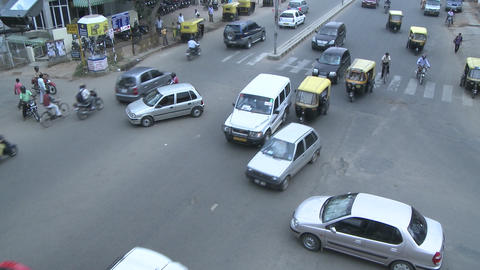 Vehicles and motorbikes pass through a busy intersection that has no directional signals Footage