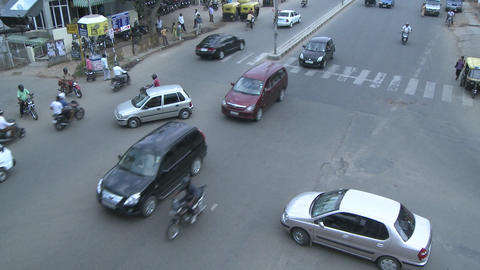 Vehicles and motorbikes pass through a busy intersection... Stock Video Footage