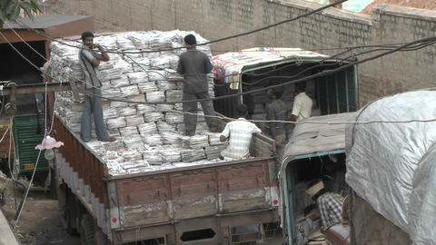 Workers transfer stacks of papers from one truck to another Stock Video Footage