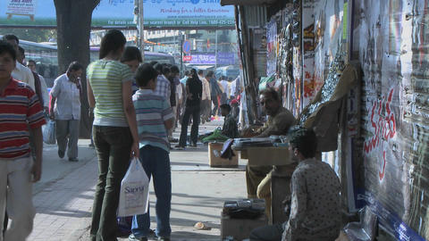 A young boy wants to buy something from a street vendor, and his mother buys it for him Footage