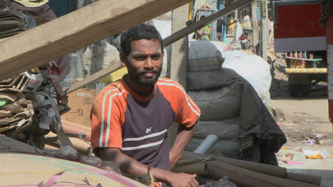 A young man sits and smiles as others work around him Stock Video Footage