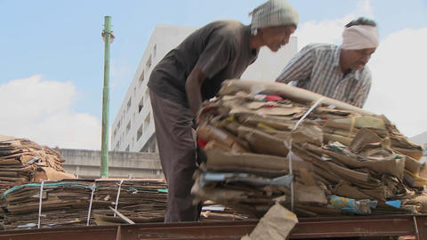 Two men are rolling a bale of cardboard on a truck Stock Video Footage