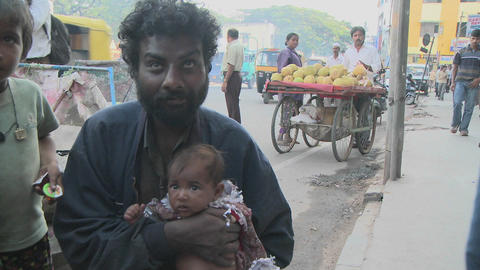 People on an Indian street watch something above their heads, then a man holding a baby smiles, gets Footage